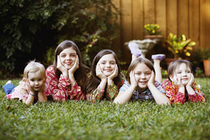 5_mixed_ages_girls_laying_on_grass_together_300_pixels